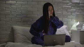 Zmęczona kobiety masowania szyja, siedzieć niewygodny na łóżku gdy pracujący na laptopie zdjęcie wideo