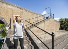 Zmęczona młodej kobiety woda pitna na schodkach Obraz Royalty Free