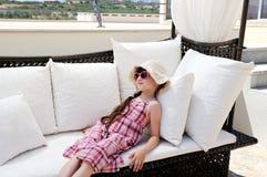 Zmęczona mała dziewczynka relaksuje na tarasowej otomanie Fotografia Stock