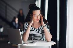 Zmęczona pamiętająca kobieta myśleć o sposobie uzupełniać zadanie Piękna kobieta ma migrenę podczas przerwy w kawiarni zdjęcie royalty free