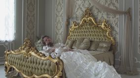 Zmęczona piękna kobieta w balowej togi skoku na szerokim łóżku zdjęcie wideo