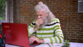 Zmęczona pracująca starsza caucasian samiec jest ziewająca jego głowę z jego, zakrywająca i relaksująca ręki podczas gdy siedzący zbiory wideo