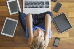 Zmęczona smutna chłopiec z pastylkami, telefony komórkowi, laptop wszystko wokoło Odgórny widok Edukacja, uczenie, technologia, n Zdjęcie Stock