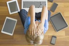 Zmęczona smutna chłopiec z pastylkami, telefony komórkowi, laptop wszystko wokoło w domu Odgórny widok Edukacja, uczenie, technol Obraz Royalty Free
