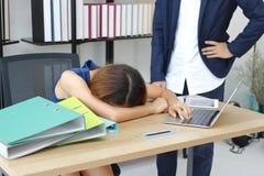 Zmęczona zapracowana młoda Azjatycka biznesowej kobiety chyłu puszka głowa na biurku przeciw gniewnemu szefowi w biurze obrazy royalty free