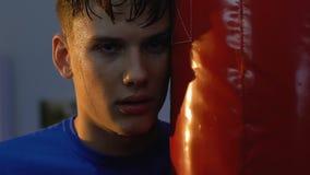 Zmęczonego nastoletniego boksera przyglądająca kamera stoi blisko uderzać pięścią torbę, sport woli władza zbiory wideo