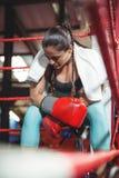 Zmęczony żeński boksera obsiadanie w pierścionku fotografia stock