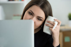 Zmęczony żeński pracownik przy miejscem pracy w biurowej trzyma filiżance herbata Obraz Royalty Free