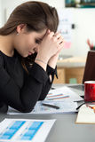 Zmęczony żeński pracownik przy miejscem pracy w biurowej trzyma filiżance herbata Zdjęcie Stock