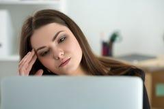 Zmęczony żeński pracownik przy miejscem pracy w biurowym macaniu jej głowa Zdjęcie Royalty Free