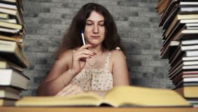 Zmęczony żeńskiego ucznia czytanie wśród książek Zadumany młodej kobiety obsiadanie przy stołem z stosem książka dalej i czytanie zdjęcie wideo