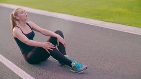 Zmęczony biegacza obsiadanie na asfaltowej drodze Skołowany żeński biegacz oddycha mocno zbiory wideo