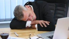 Zmęczony biznesmen z laptopu spadać uśpiony w biurze zbiory