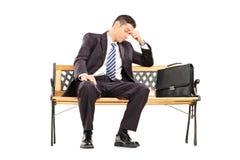 Zmęczony biznesmena obsiadanie na ławce Zdjęcia Stock
