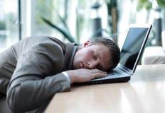 Zmęczony biznesowego mężczyzna dosypianie na jego laptopie przy biurem Zdjęcia Royalty Free