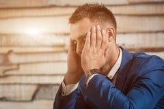 Zmęczony biznesowy mężczyzna trzyma jego głowę na rękach przy miejscem pracy w biurze Śpiący pracownik wcześnie w ranku po nocnej Obraz Royalty Free