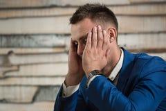Zmęczony biznesowy mężczyzna trzyma jego kierowniczy na brzęczeniach przy miejscem pracy w biurze Zdjęcie Stock