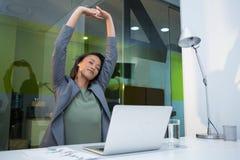 Zmęczony bizneswoman rozciąga ona up przy biurkiem ręki Obraz Royalty Free