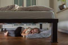 Zmęczony dziewczyny dosypianie pod łóżkiem z misiem Zdjęcia Stock