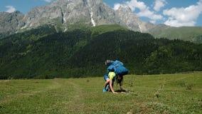 Zmęczony i słaby turysta z ciężkim plecakiem wstaje od ziemi na podwyżce przeciw tłu piękny obraz stock
