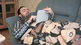 Zmęczony i zdegustowany młody człowiek używa pastylkę w łóżku zbiory