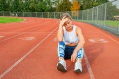 Zmęczony kobieta biegacz bierze odpoczynek po bieg obsiadania na bieg fotografia stock