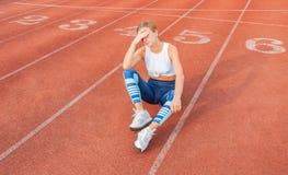 Zmęczony kobieta biegacz bierze odpoczynek po bieg obsiadania na bieg zdjęcia stock
