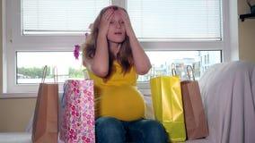 Zmęczony kobieta w ciąży z kolorowymi torbami siedzi na kanapa plecy domu po robić zakupy zbiory wideo