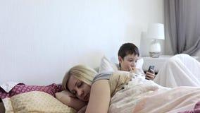 Zmęczony kobiety matki dosypianie, jej słońca obsiadanie w łóżku i bawić się mobilne gry na gadżecie, smartphone Brak uwaga zbiory