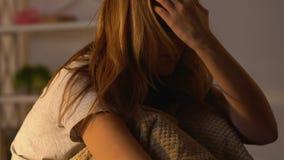 Zmęczony kobiety obsiadanie na łóżku w pokoju, z trudem budzi wcześnie w ranku, sunbeams zbiory