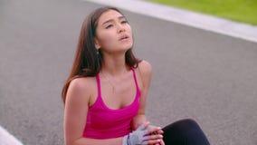 Zmęczony kobiety obsiadanie na drodze Skołowany kobiety oddychanie po biegać ćwiczenie zbiory wideo