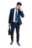 Zmęczony korporacyjny pracownik po pracy ma migrenę fotografia stock