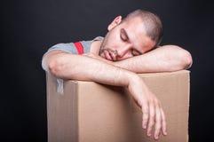 Zmęczony lub skołowany wnioskodawca faceta dosypianie na kartonie obraz stock