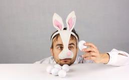 Zmęczony mężczyzna patrzeje jajko w maskowym Wielkanocnym króliku Zdjęcia Royalty Free