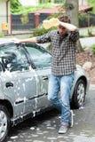 Zmęczony mężczyzna podczas samochodowego cleaning Zdjęcia Royalty Free