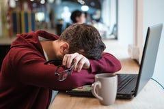 Zmęczony mężczyzna trzyma szkła podczas gdy śpiący przy biurowym biurkiem obraz stock