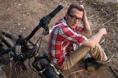 Zmęczony mężczyzna z łamanym rowerem w zadumie Zdjęcia Royalty Free