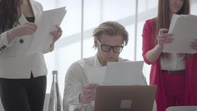 Zmęczony mężczyzny obsiadanie w wygodnym biurze z netbook przy stołem egzamininuje dokumenty które dają żeńscy koledzy zbiory