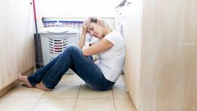 Zmęczony młodej kobiety cierpienie od migreny obsiadania na podłoga przy pralnią Obraz Royalty Free