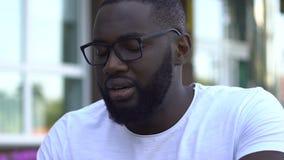 Zmęczony młody afroamerykański freelancer pracuje na projekcie, ostatecznego terminu pojęcie zdjęcie wideo