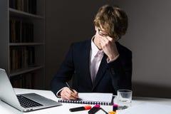 Zmęczony młody biznesmen naciera jego oczy przy miejscem pracy Obrazy Stock