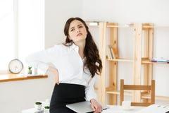 Zmęczony młody bizneswomanu cierpienie od długiego czasu obsiadania przy komputerowym biurkiem w biurze Zdjęcia Stock
