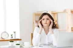 Zmęczony młody bizneswomanu cierpienie od długiego czasu obsiadania przy komputerowym biurkiem w biurze Fotografia Royalty Free