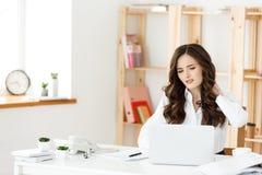 Zmęczony młody bizneswomanu cierpienie od długiego czasu obsiadania przy komputerowym biurkiem w biurze Obraz Stock