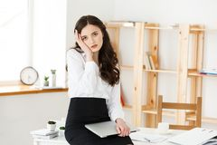 Zmęczony młody bizneswomanu cierpienie od długiego czasu obsiadania przy komputerowym biurkiem w biurze Obraz Royalty Free
