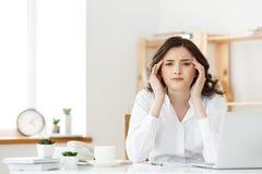 Zmęczony młody bizneswomanu cierpienie od długiego czasu obsiadania przy komputerowym biurkiem w biurze Fotografia Stock
