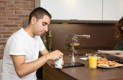 Zmęczony młody człowiek z filiżanką kawy w śniadaniu obraz stock