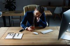zmęczony pijący biznesmena obsiadanie z szkłem whisky obrazy royalty free