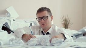 Zmęczony pracownik przy biurkiem w ogromnych stosach papiery podpisuje wiele dokumenty pojęcia podłączeniowi pomysłu internety dz zdjęcie wideo