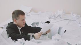 Zmęczony pracownik siedzi w stosie papiery w jego biurze Podczas pracy urzędnik doświadcza zbiory